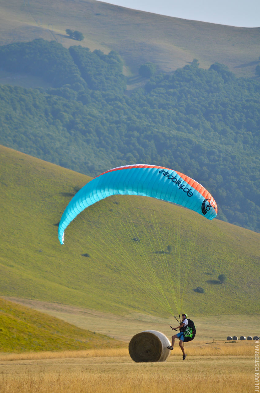 real people, leisure activity, adventure, extreme sports, day, lifestyles, parachute, landscape, men, outdoors, mountain, field, sport, nature, transportation, full length, skill, flying, scenics, paragliding, sky, people