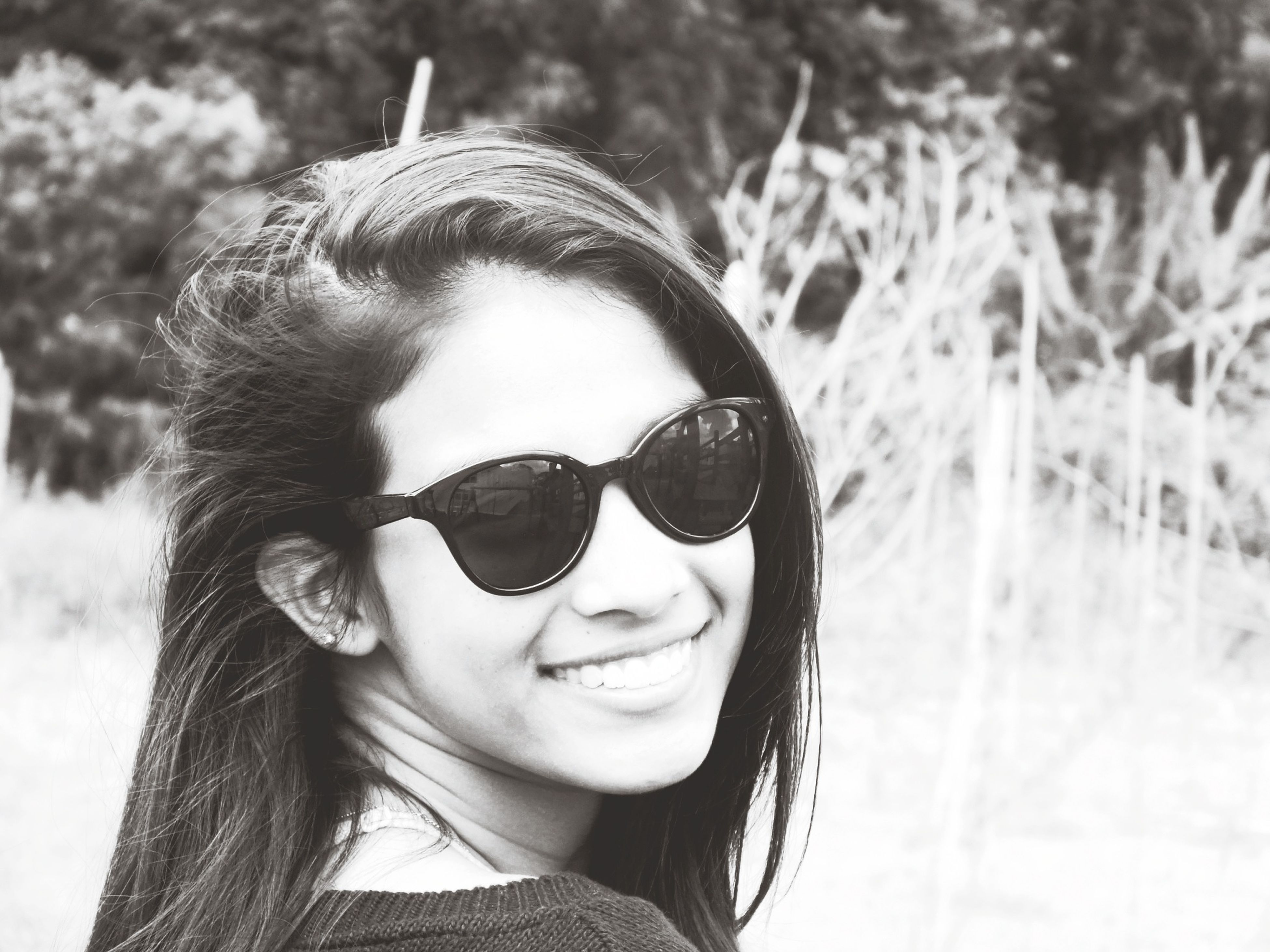 looking at camera, portrait, person, headshot, young adult, front view, focus on foreground, lifestyles, smiling, young women, close-up, sunglasses, leisure activity, head and shoulders, human face, happiness, day