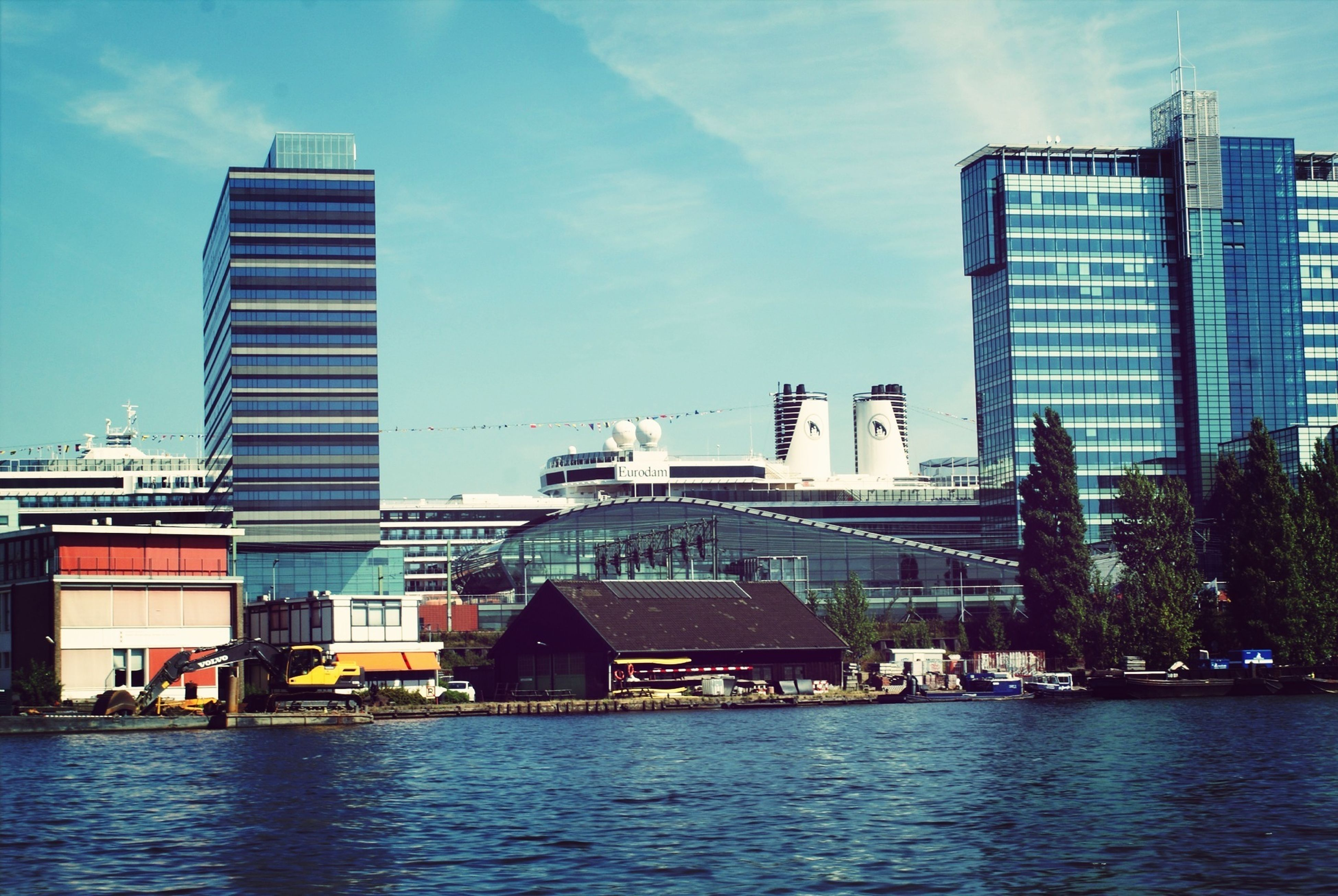 architecture, building exterior, built structure, waterfront, water, sky, city, river, modern, tower, tall - high, travel destinations, travel, cloud - sky, building, office building, capital cities, day, skyscraper, outdoors