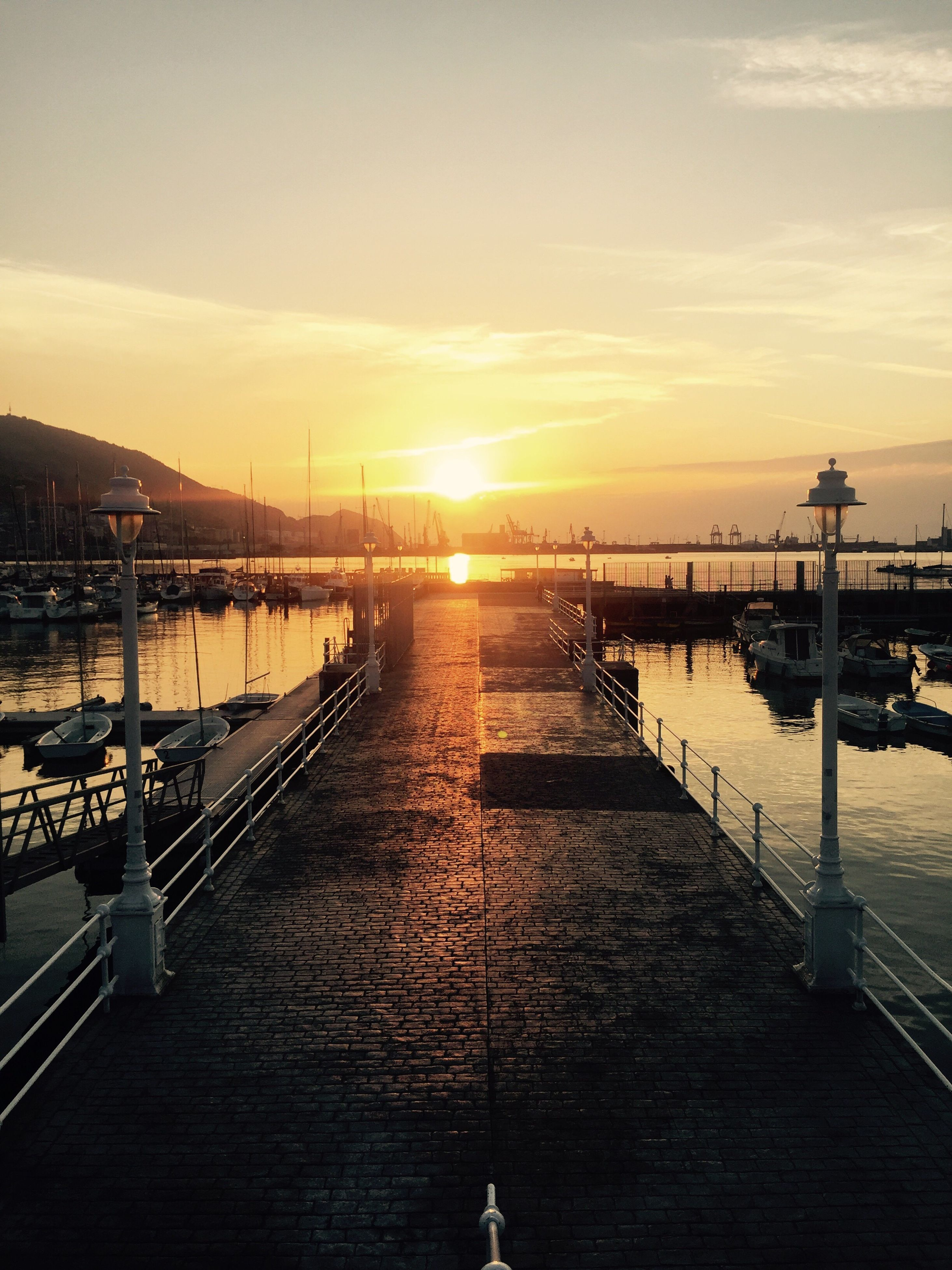 sunset, water, sun, sky, scenics, sunbeam, sunlight, beauty in nature, tranquil scene, nature, tranquility, bridge - man made structure, pier, reflection, sea, outdoors, no people, built structure, cloud - sky, travel destinations, harbor, silhouette, architecture, jetty, nautical vessel, day