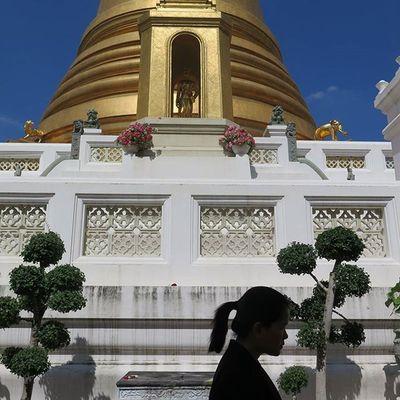 Worshipper walking by the golden chedi of Wat Bowonniwet. Bangkok Thailand Travel Travelshots Everydayasia Everydaylife Explorebkk Streetphotography Cityscene Peoplewatching Blueskies Temple Seeninthecity Feel The Journey