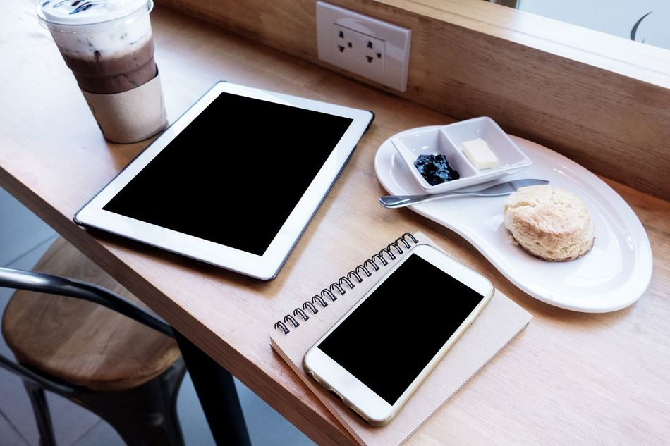Breakfast Coffee - Drink Coffee Cup Communication Day Digital Tablet Drink Food Food And Drink Freshness Frothy Drink High Angle View Indoors  Mobile Phone No People Plate Portable Information Device Refreshment Smart Phone Still Life Table Technology Touch Screen Wireless Technology Wood - Material
