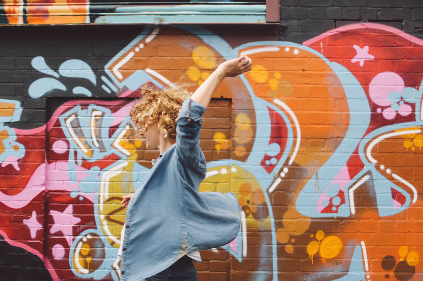 Art Blonde Brighton Built Structure Casual Clothing Creativity Curly Hair Day Girl Graffiti Graffiti Graffiti Art Joyful Jumping Leisure Activity Lifestyles Multi Colored Orange Color Painting Playful Spinning Street Art People And Places