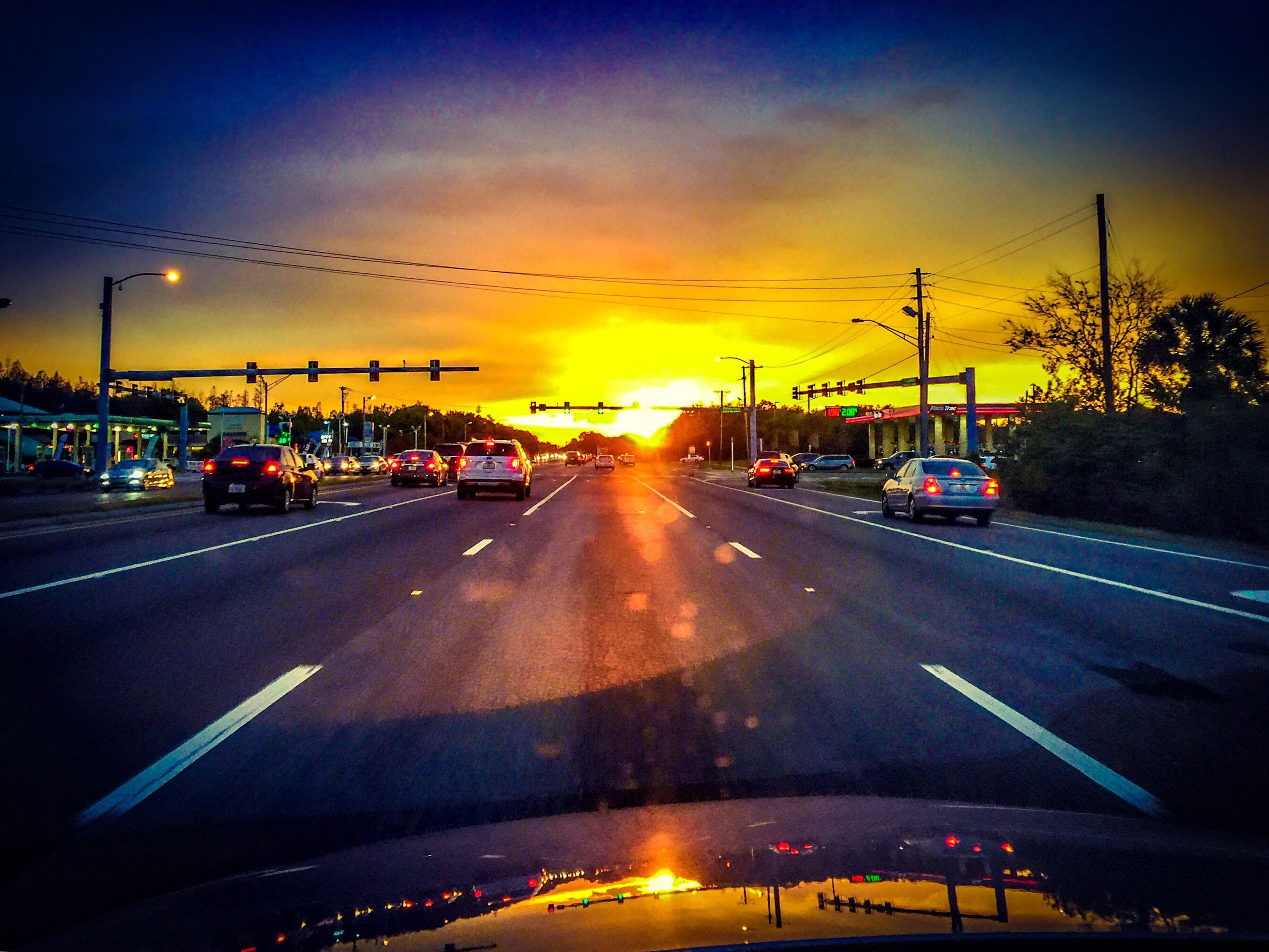 transportation, sunset, car, mode of transport, land vehicle, road, sky, traffic, on the move, road marking, orange color, street, sun, cloud - sky, the way forward, travel, street light, diminishing perspective, windshield, outdoors