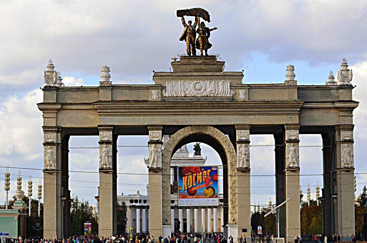 architecture, statue, built structure, cloud - sky, gate, animal representation, tourism, travel destinations, sculpture, city gate, arch, history, large group of people, sky, building exterior, triumphal arch, outdoors, low angle view, day, architectural column, city, people, adult