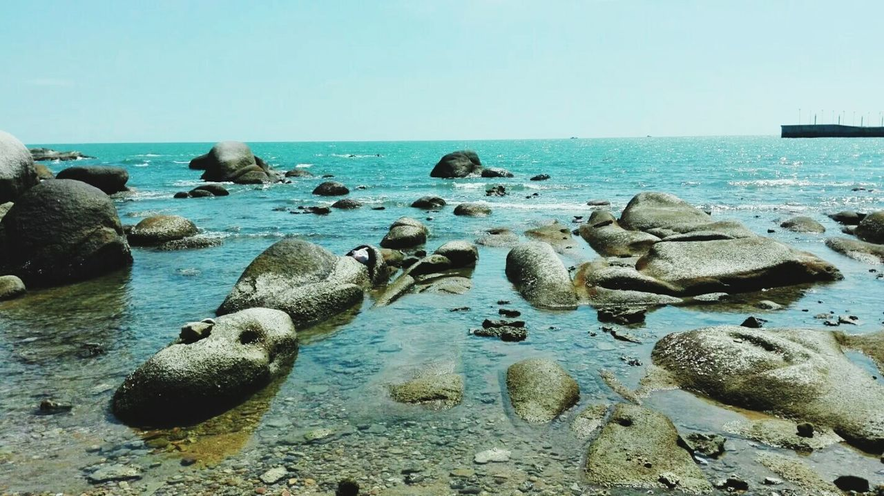 sea, horizon over water, water, tranquil scene, scenics, clear sky, tranquility, beauty in nature, beach, rock - object, tourism, nature, travel destinations, non-urban scene, blue, calm, seascape, sky, shore, vacations, day, outdoors, rocky coastline, coastline, summer, majestic, surface level, no people, distant, geology