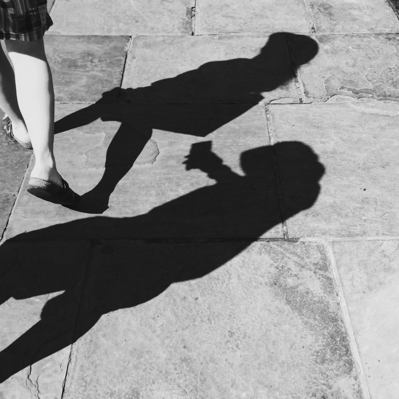 shadow, sunlight, real people, low section, focus on shadow, leisure activity, one person, human leg, lifestyles, day, outdoors, standing, skill, friendship, human hand, people