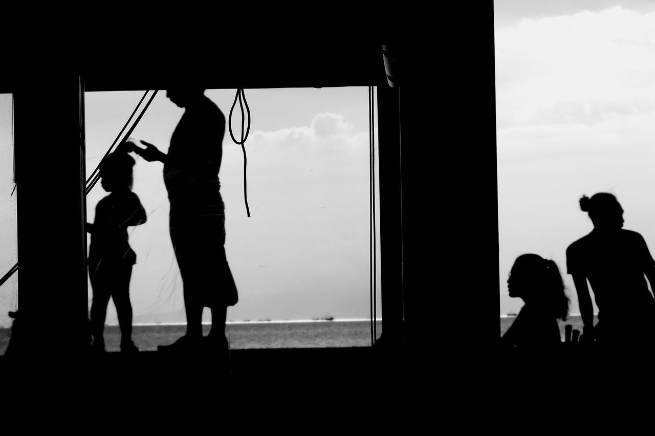 real people, silhouette, men, window, lifestyles, togetherness, leisure activity, standing, childhood, day, boys, women, sky, bonding, indoors, full length, friendship, window washer, people