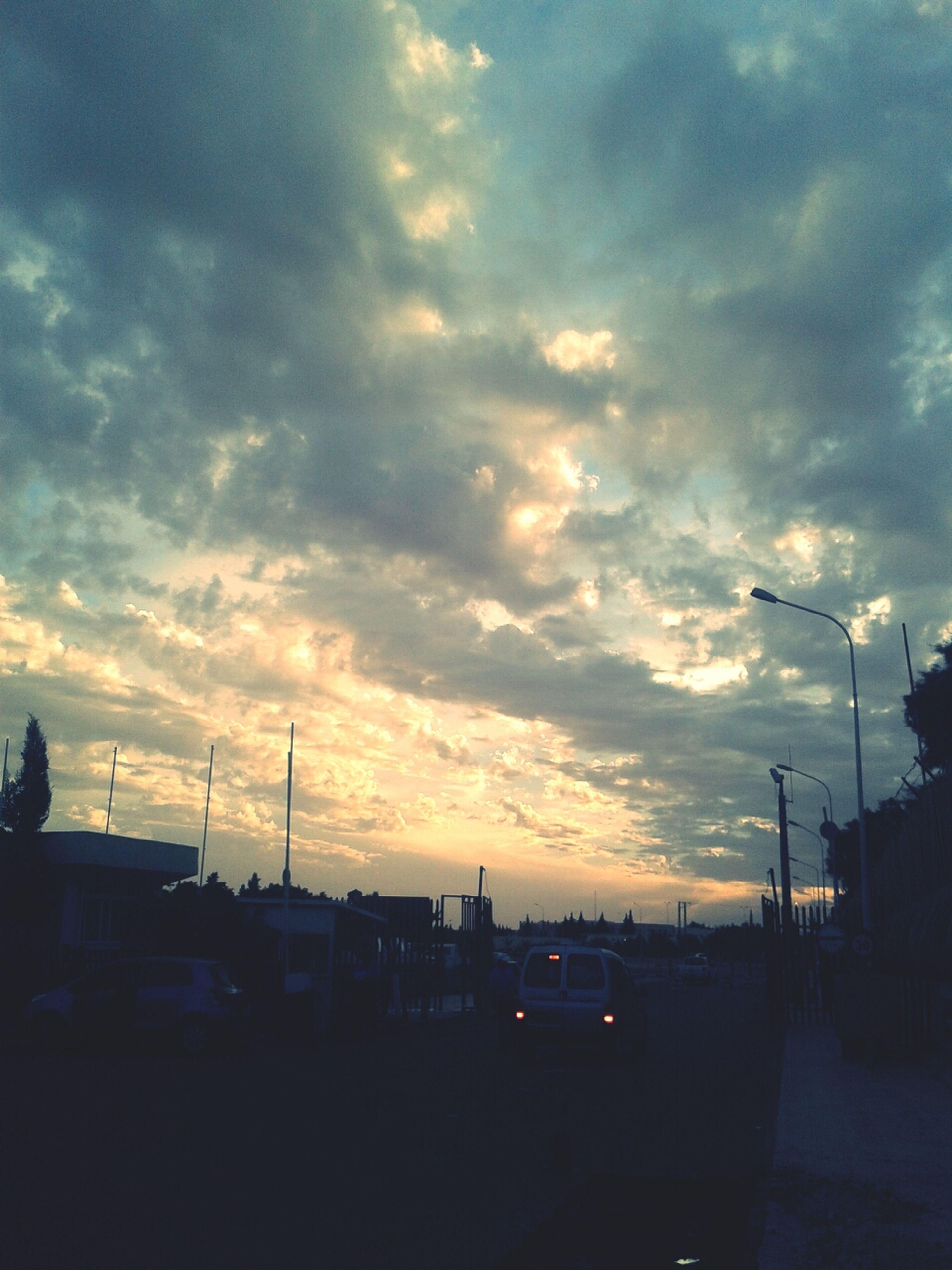 sky, transportation, sunset, car, cloud - sky, silhouette, mode of transport, land vehicle, cloudy, street light, road, street, cloud, dusk, building exterior, built structure, outdoors, nature, parking lot, city