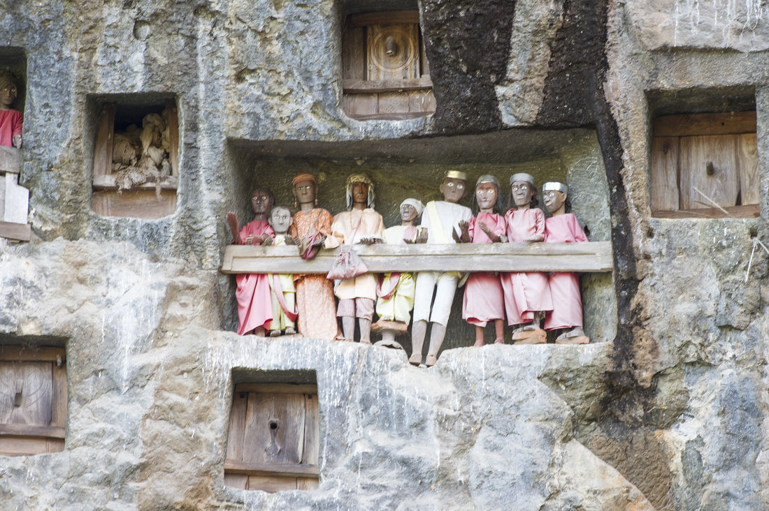 Burial site at Lemo, North Toraja, Indonesia. Adult Architecture Building Exterior Built Structure Burial Day Horizontal Lemo. Men North Toraja Outdoors People Person Religion Spirituality Statue Tau Tau Togetherness
