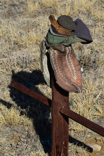 Grave site with old boot Graveyard Cowboy Boot Cross Metal Rust Rural No People Day Outdoors Close-up