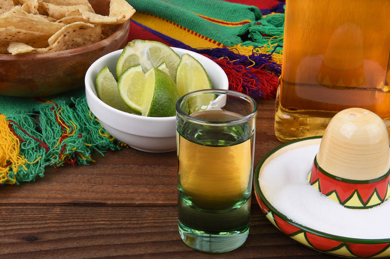 Tequila shot with limes, salt, chips and Mexican blanket. Great for Cinco de Mayo themed projects or Mexican restaurants. Blanket Bottle Cinco De Mayo Corn Chips Drink Freshness Limes Mexico No People Salt Shot Glass Sombrero Tequila