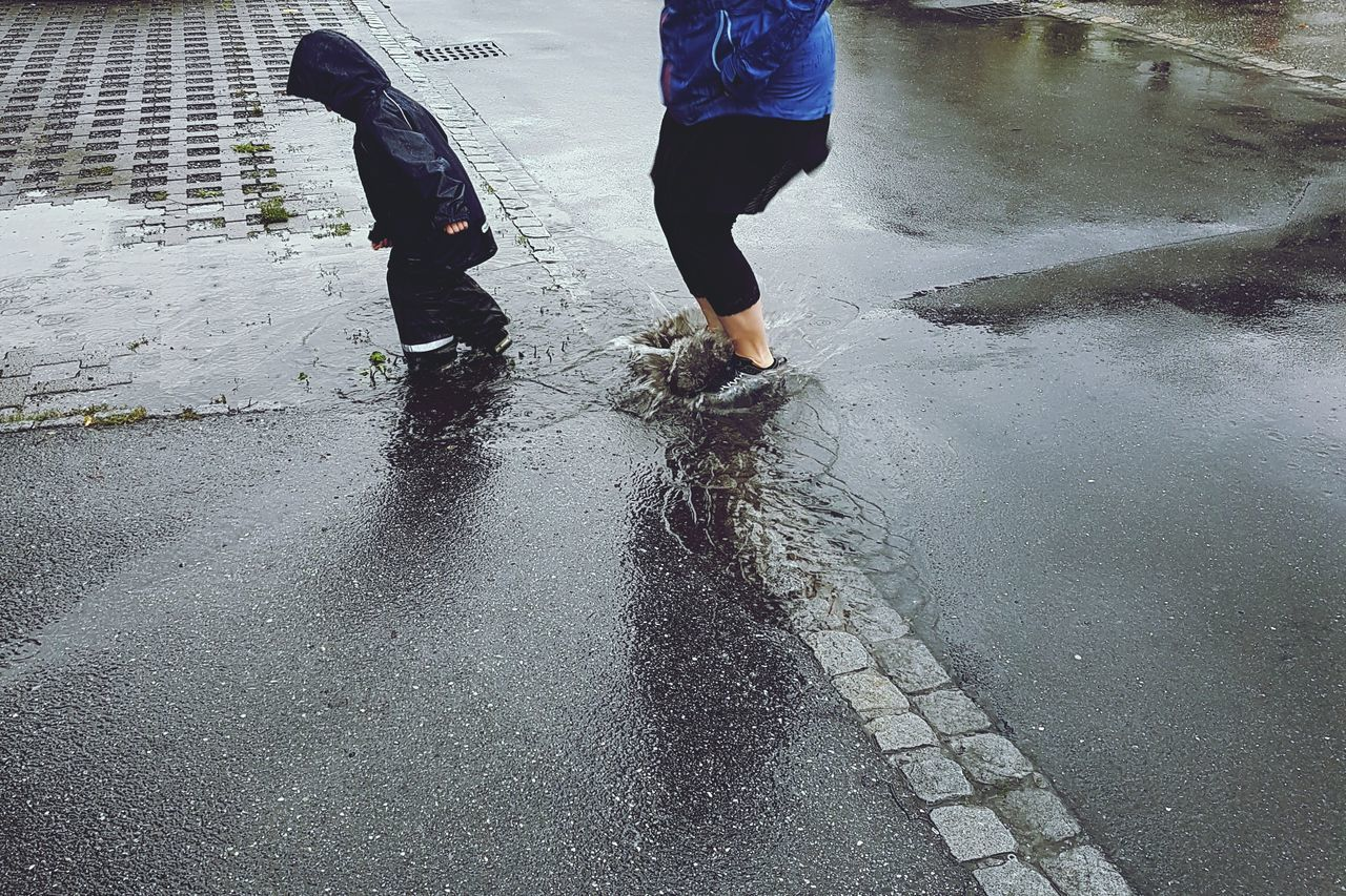 wet, puddle, rain, rainy season, low section, real people, walking, two people, water, weather, reflection, road, men, human leg, day, lifestyles, outdoors, human body part, adult, people, adults only