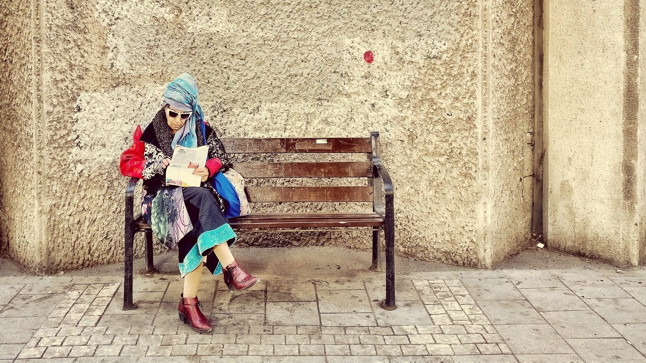 sitting, only women, one person, full length, front view, scarf, outdoors, one woman only, day, people, portrait, adult, adults only, childhood, one young woman only, warm clothing, young adult
