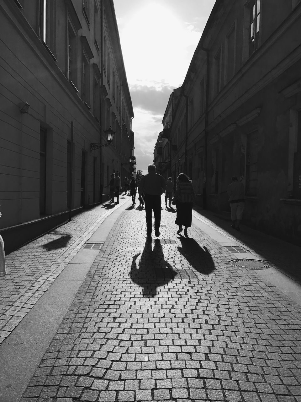 walking, architecture, building exterior, full length, built structure, street, real people, city, shadow, sunlight, outdoors, two people, men, day, women, friendship, sky, people, adult