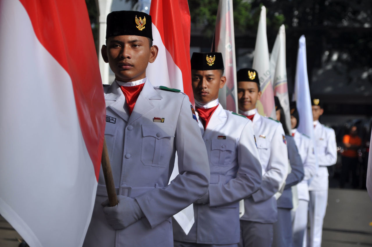 Flag Raises INDONESIA Adult Day Flag Front View Garuda Helmet Indonesia Flag Men Military Military Uniform Occupation Outdoors People Portrait Pride Real People Red And White Standing Teamwork Togetherness Uniform Young Adult