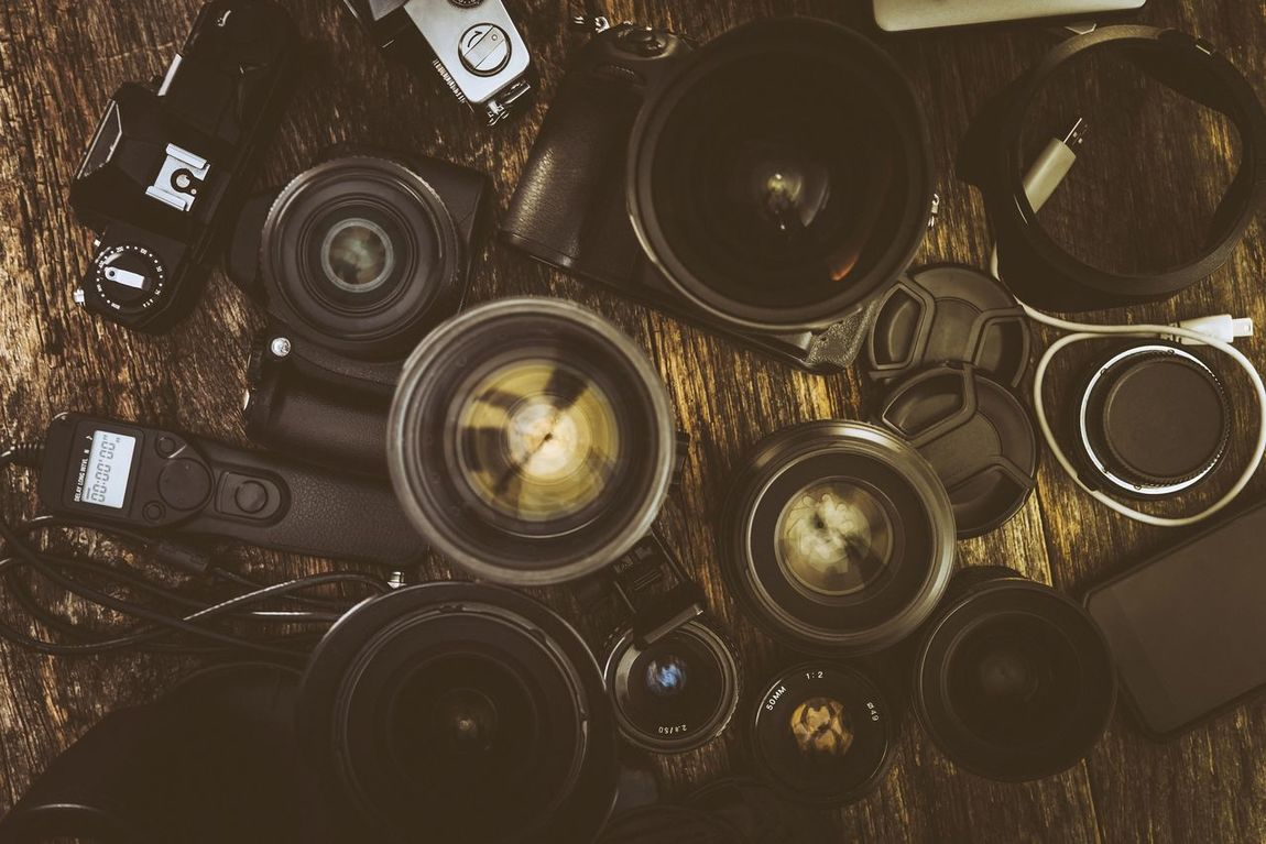 Photography Equipment. Vintage and Modern Photo Equipment on Wooden Table Aerosol Can Aged Camera - Photographic Equipment Choice Close-up Day History Imaging Indoors  Large Group Of Objects No People Photo Photographer Photography Variation Vintage