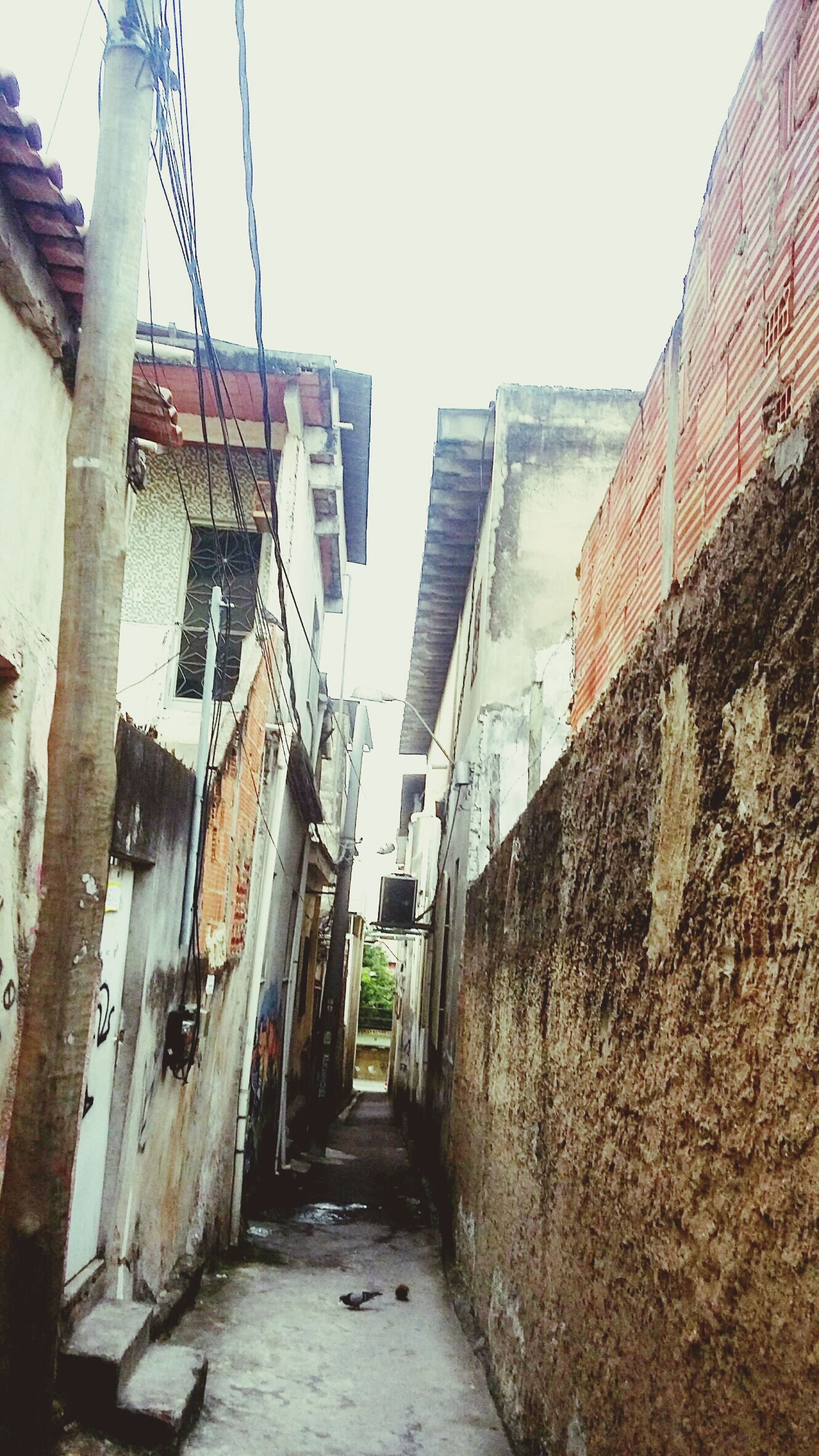 architecture, building exterior, built structure, the way forward, residential structure, residential building, building, street, clear sky, narrow, house, diminishing perspective, alley, city, day, sky, wall - building feature, outdoors, road, vanishing point