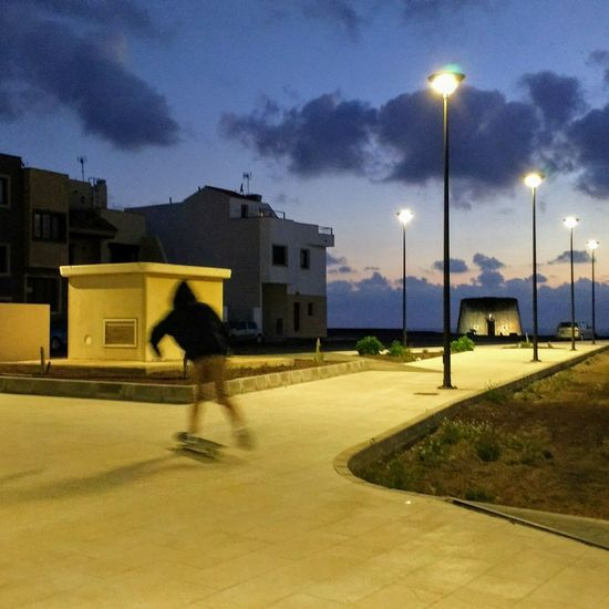 Evening skating in El Cotillo - Fuerteventura Street Light Cloud - Sky One Person City Built Structure Sky Outdoors People Adult Lightning One Man Only Adults Only Evening Light Photography Evening Stroll Evening Lights El Cotillo Fuerteventuraexperience Colors Of Life 💜💛💚💙❤💋 Pattern 😘 Travel Destinations Fuerteventura Night Low Angle View Skating In The Dark Skating Is Life EyeEmNewHere The Street Photographer - 2017 EyeEm Awards