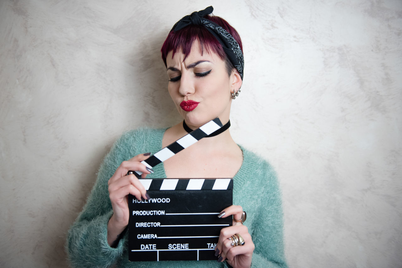 Young Woman Holding Film Slate Against Wall