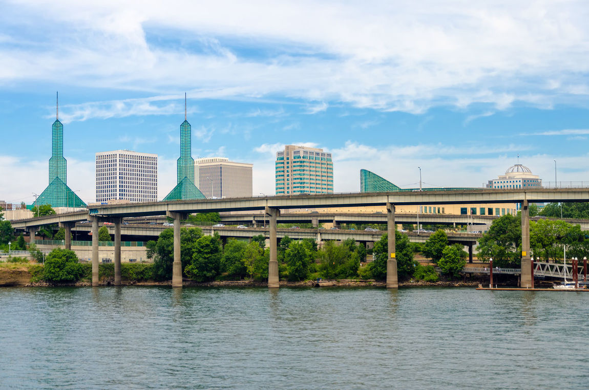View of convention center and infrastructure in Portland, Oregon America Architecture Center City Convention Day Downtown Glass Industrial Modern Oregon Outdoors Portland River Skyline Sunny Towers Trees Urban USA View Water Waterfront West Willamette
