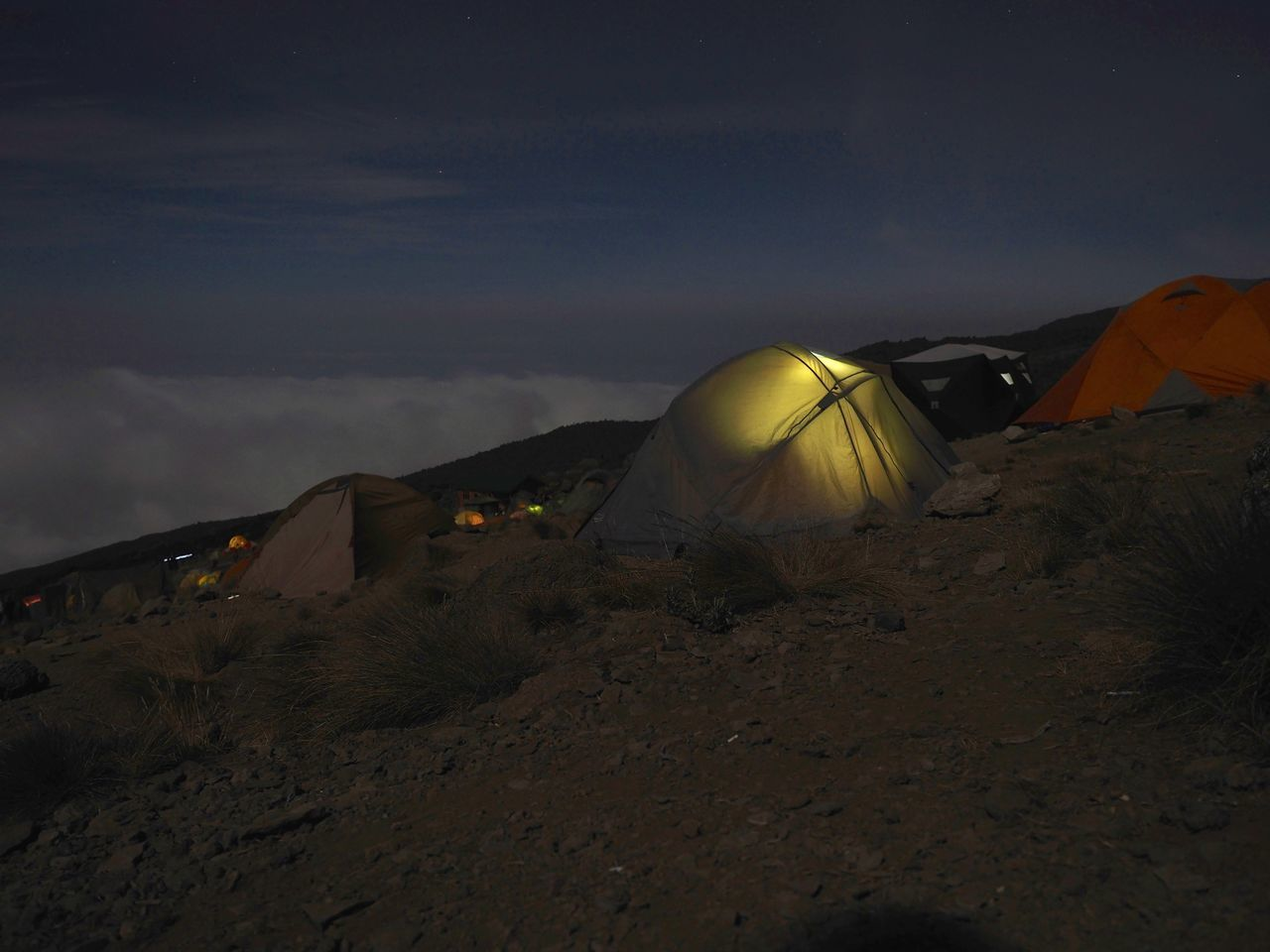 Low angle view of illuminated tents on hill at night