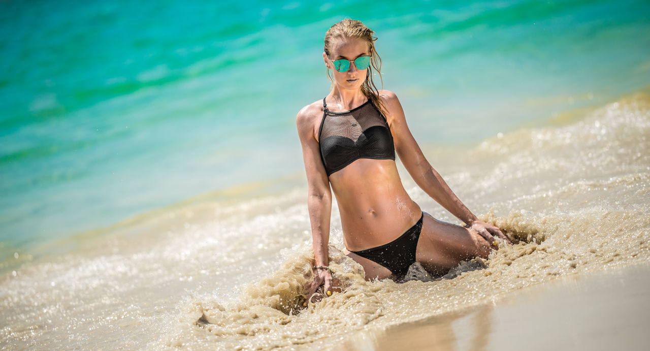 Beach Beautiful Woman Beauty Beauty In Nature Bikini Bikini Bottom Blond Hair Day Healthy Lifestyle Kneeling Kneeling In Water Leisure Activity Lifestyles Nature One Person Outdoors Portrait Real People Sea Water Young Adult Young Women