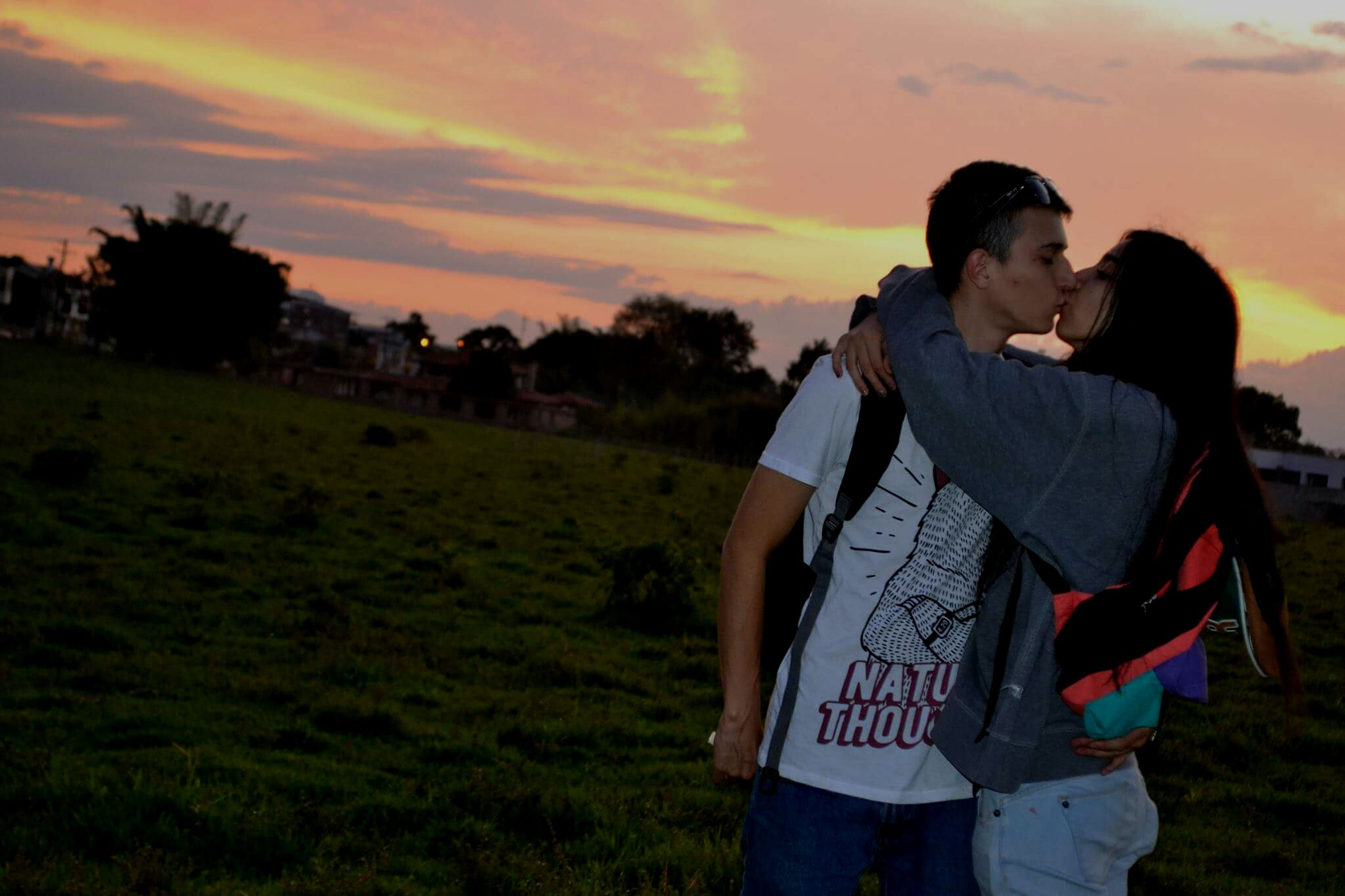 love, two people, couple - relationship, romance, heterosexual couple, sunset, young adult, sky, grass, happiness, togetherness, men, smiling, bonding, lifestyles, young women, cloud - sky, beauty, outdoors, adults only, adult, people, real people, beauty in nature, nature