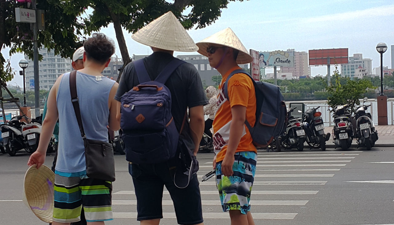 Backpack tourists seeking directions in street in Da Nang, Vietnam. Backpacks Casual Clothing Conical Hats Conversations Danang Friends Friendship Han River Lifestyles Men Motorcycles Pedestrian Crossings Real People Rivers Standing Streets Three Quarter Length Tourism Tourists Travel Vietnam Young Adult