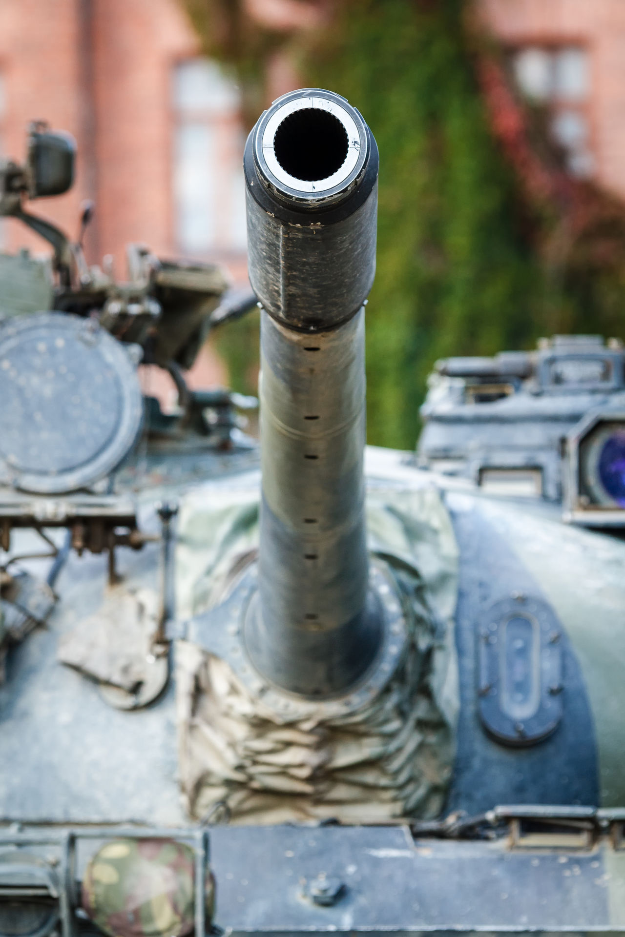 War tank turret closeup. A barrel of a military tank pointed to the sky. Old barrack building on the background. Aggressive Armor Artistic Barrel Bolt Cannon Close-up Dangerous Day Explosive Metal Metal Industry Military No People Nut - Fastener Outdoors Tank Turret Water Weapon Weapons Of War