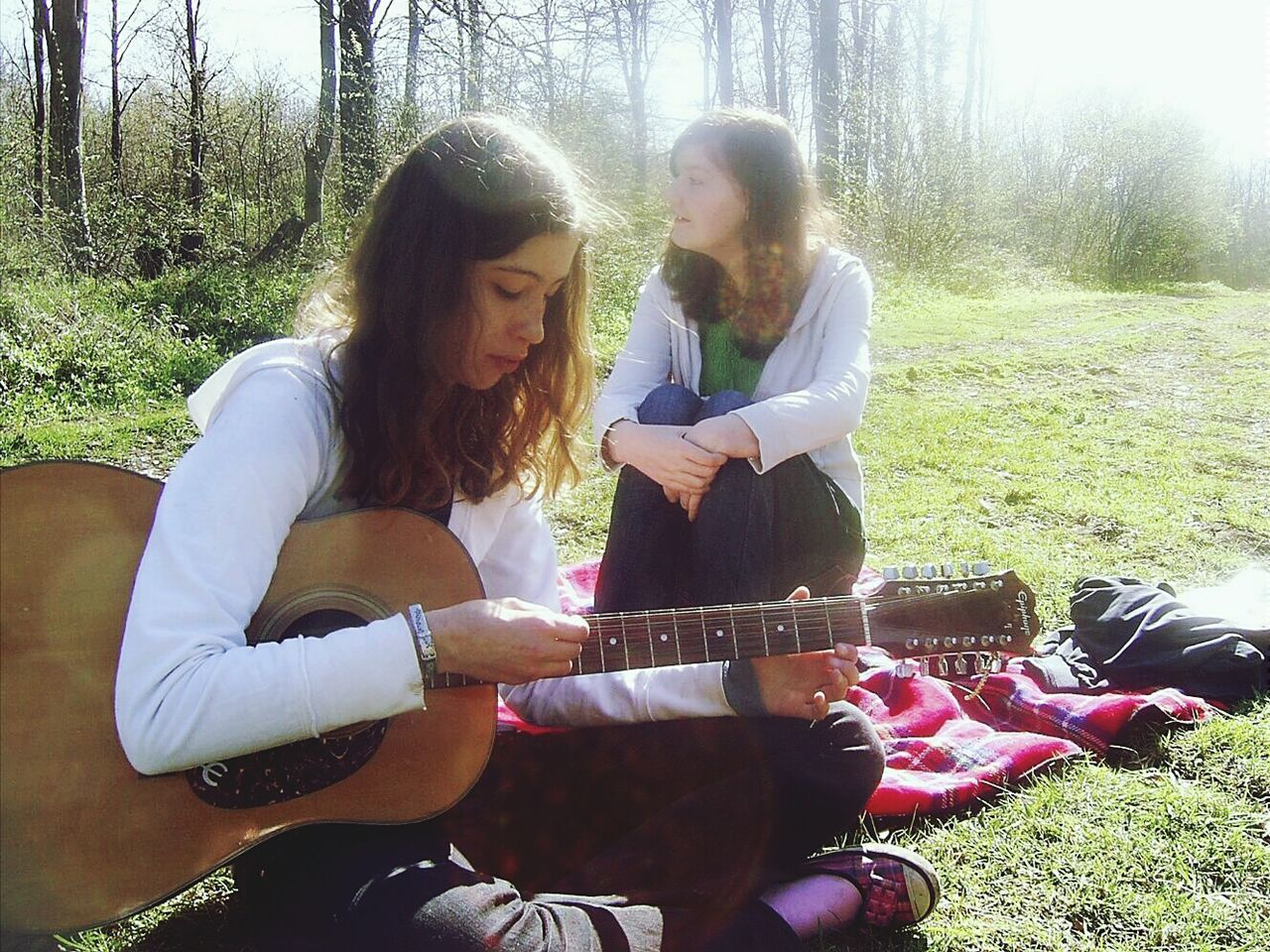 sitting, casual clothing, young women, guitar, leisure activity, real people, young adult, three quarter length, togetherness, tree, music, day, lifestyles, playing, two people, nature, grass, outdoors, musical instrument, relaxation, women, full length, plucking an instrument, smiling, musician, people