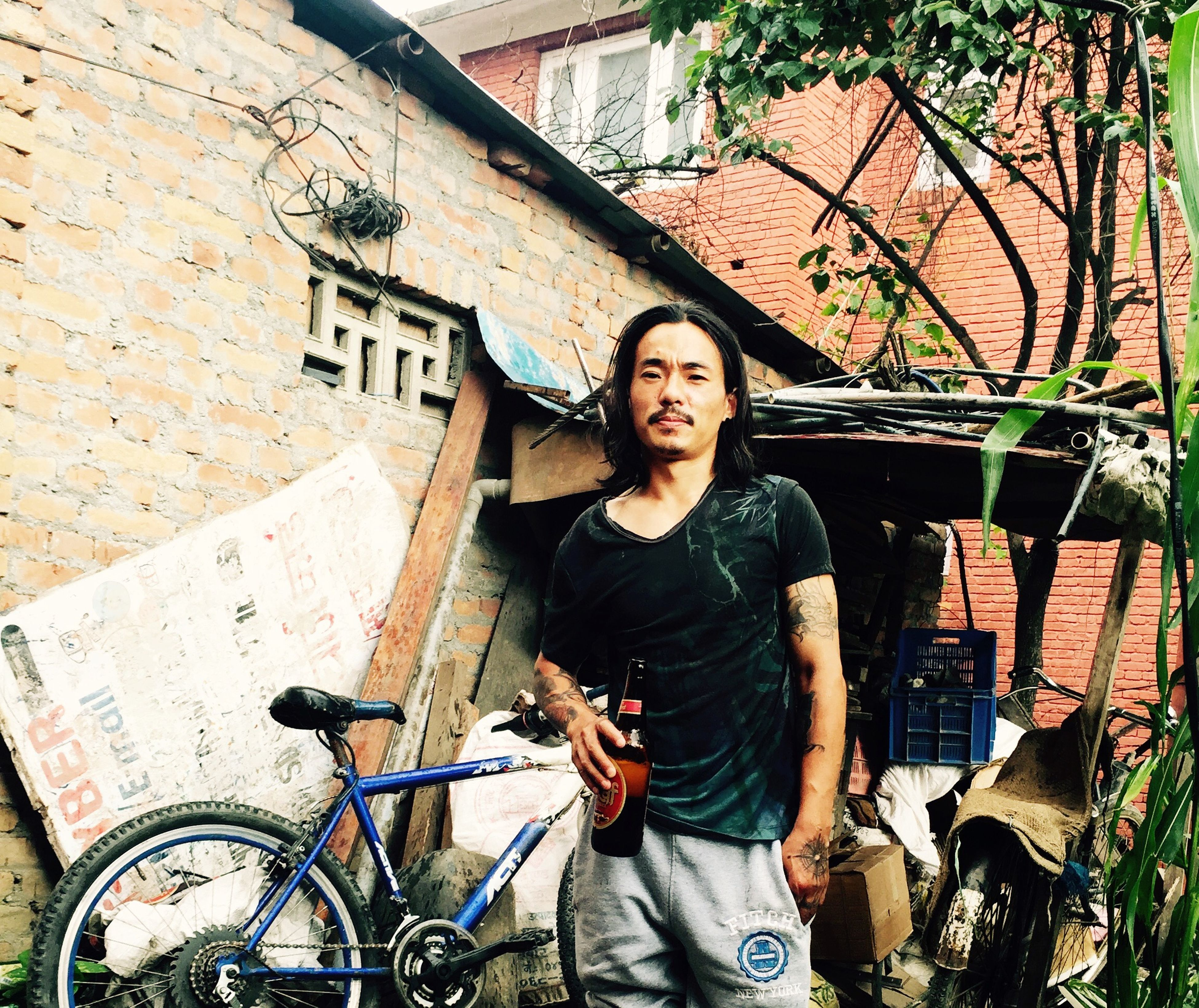 lifestyles, young adult, person, leisure activity, casual clothing, looking at camera, portrait, building exterior, architecture, young men, built structure, smiling, standing, three quarter length, waist up, front view, bicycle