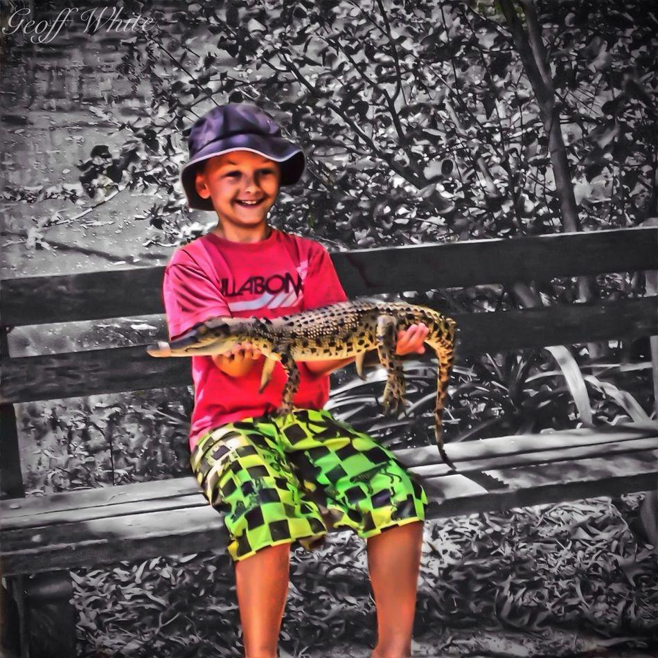 Son Riley holding a croc at Currumbin Sanctuary, colour splash