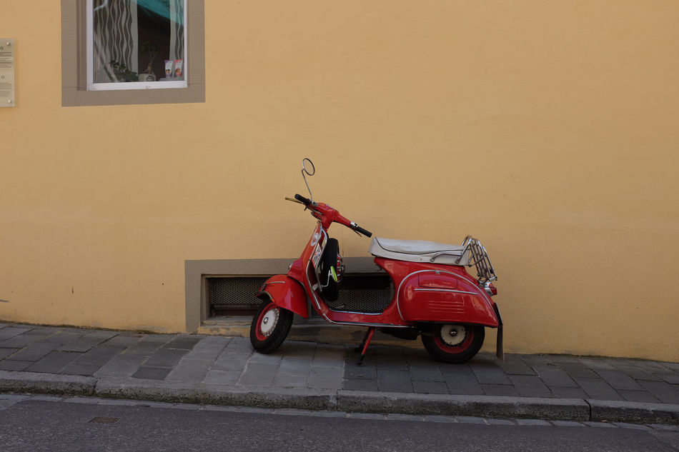 A red vespa parked on the sidewalk Architecture Building Built Structure Curb Curiosity Day Empty Exterior Footpath Moped Motorbike No People Outdoors Park Parked Parking Quiet Red Stationary Street Streetside Sunny Urban Vespa Yellow