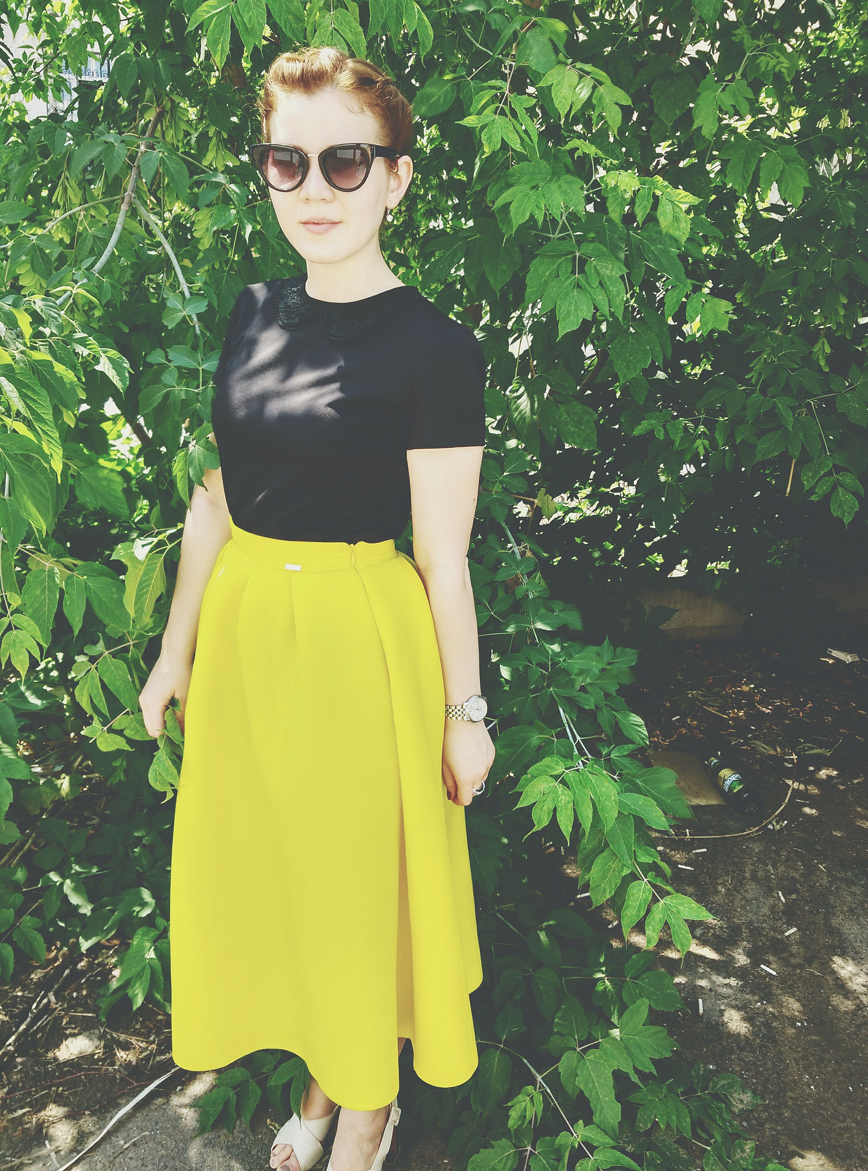 young adult, casual clothing, lifestyles, person, front view, young women, looking at camera, standing, leisure activity, portrait, three quarter length, tree, full length, smiling, sunglasses, holding, fashion
