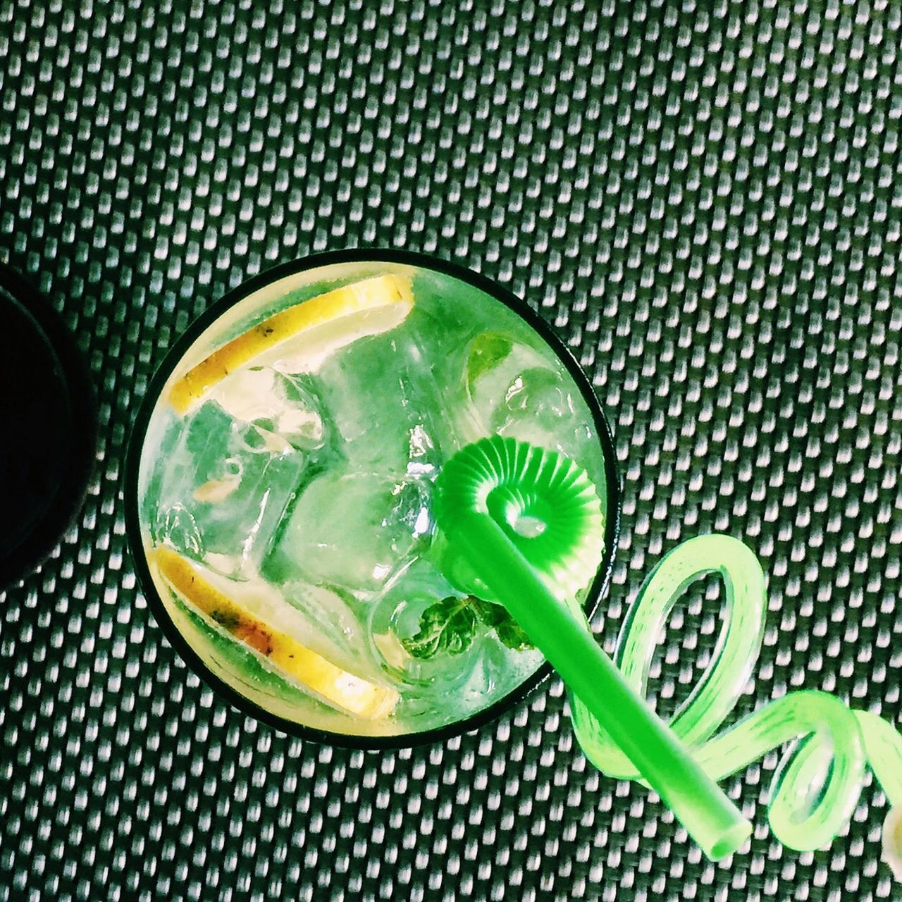 Directly Above View Of Juice With Green Spiral Straw On Table