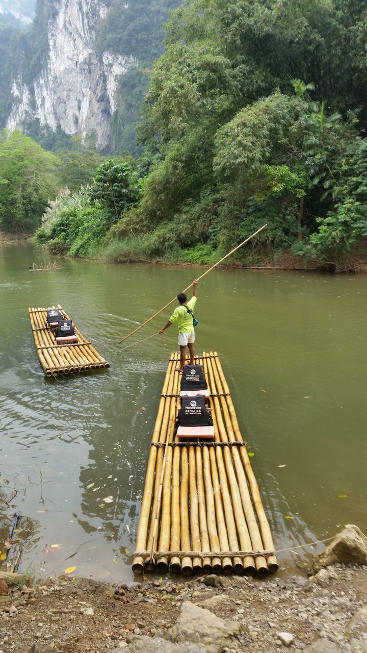 Rear View Of Man On Wooden Raft At River