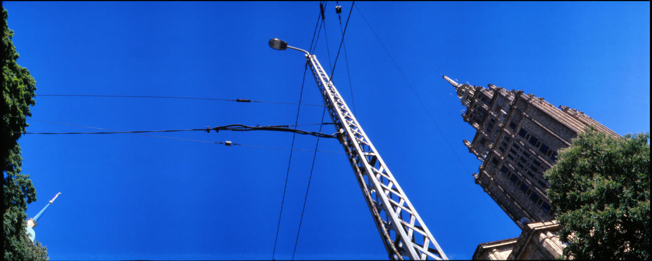 blue, low angle view, day, cable, outdoors, connection, built structure, architecture, sky, no people, clear sky, building exterior, mast, tree