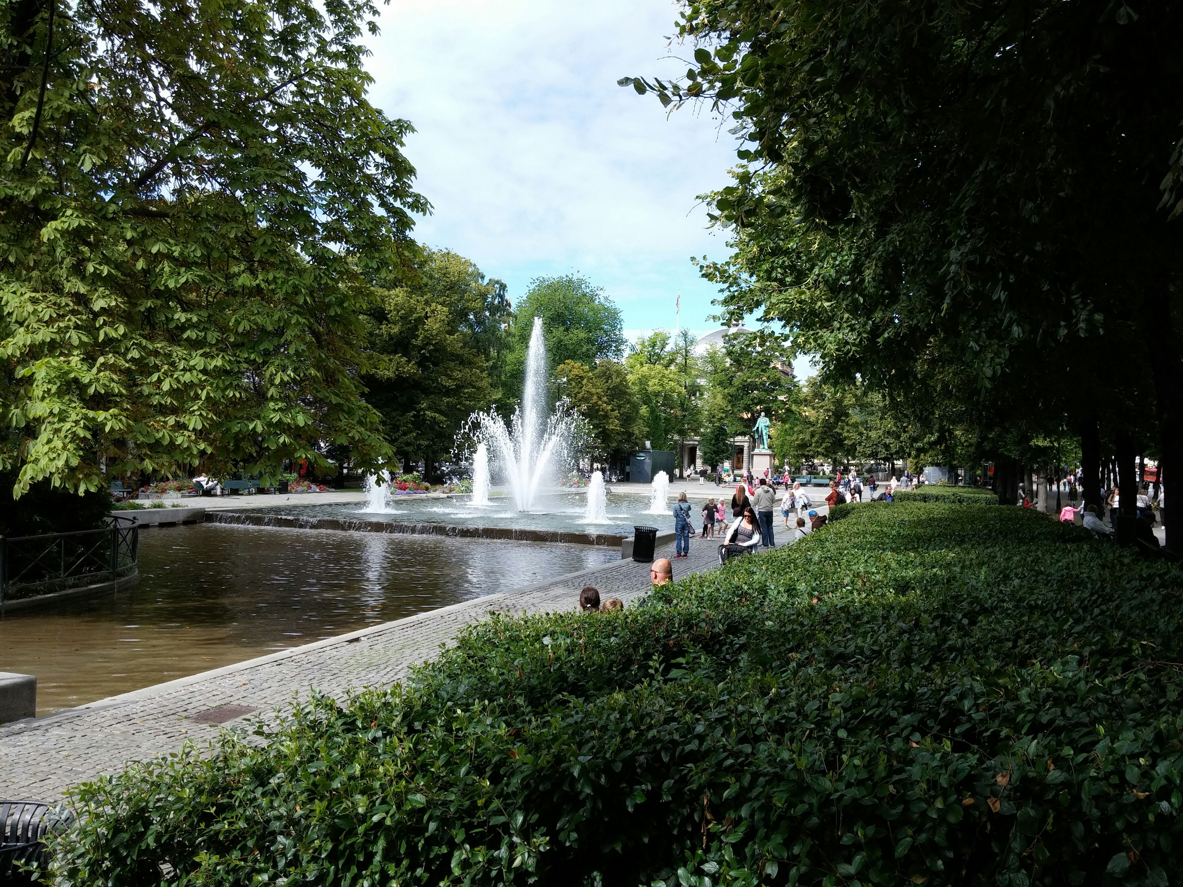 water, tree, fountain, motion, park - man made space, splashing, spraying, waterfall, green color, growth, flowing water, large group of people, long exposure, nature, incidental people, beauty in nature, sky, plant, travel destinations