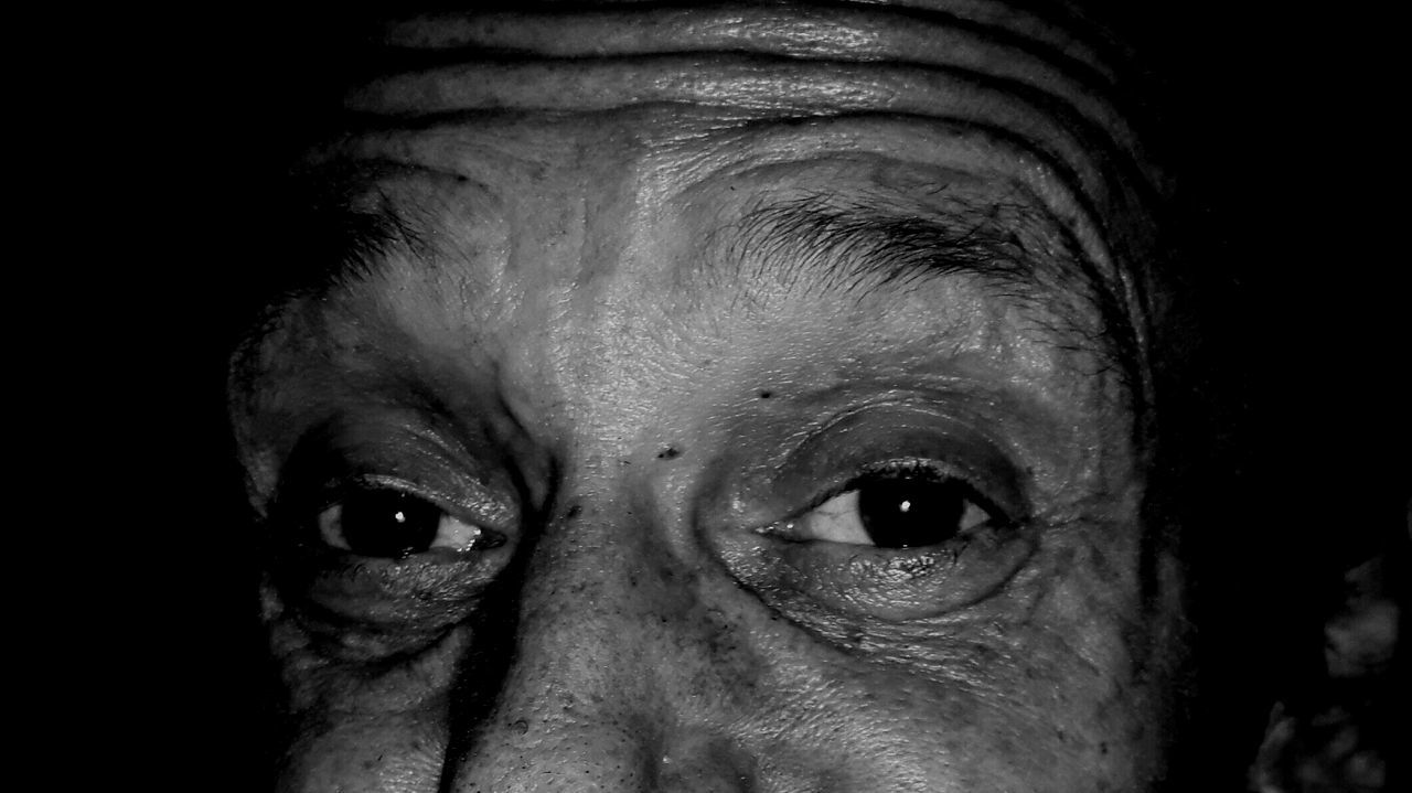 portrait, looking at camera, human face, one person, close-up, one man only, real people, human body part, senior adult, human eye, headshot, one senior man only, men, indoors, only men, eyeball, adult, day, adults only, people