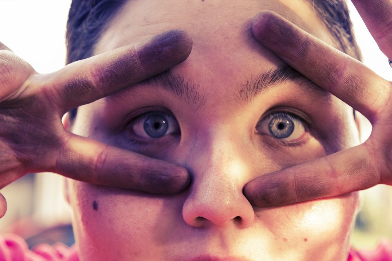 close-up, childhood, real people, looking at camera, human face, portrait, elementary age, one person, boys, outdoors, human hand, day, young adult