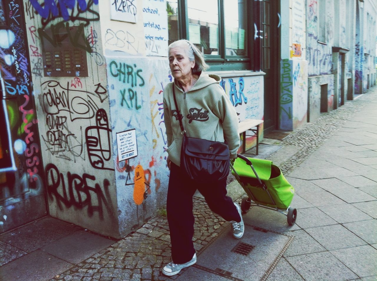real people, full length, graffiti, one person, senior adult, architecture, casual clothing, outdoors, lifestyles, text, front view, built structure, senior women, day, building exterior, standing, leisure activity, adult, people