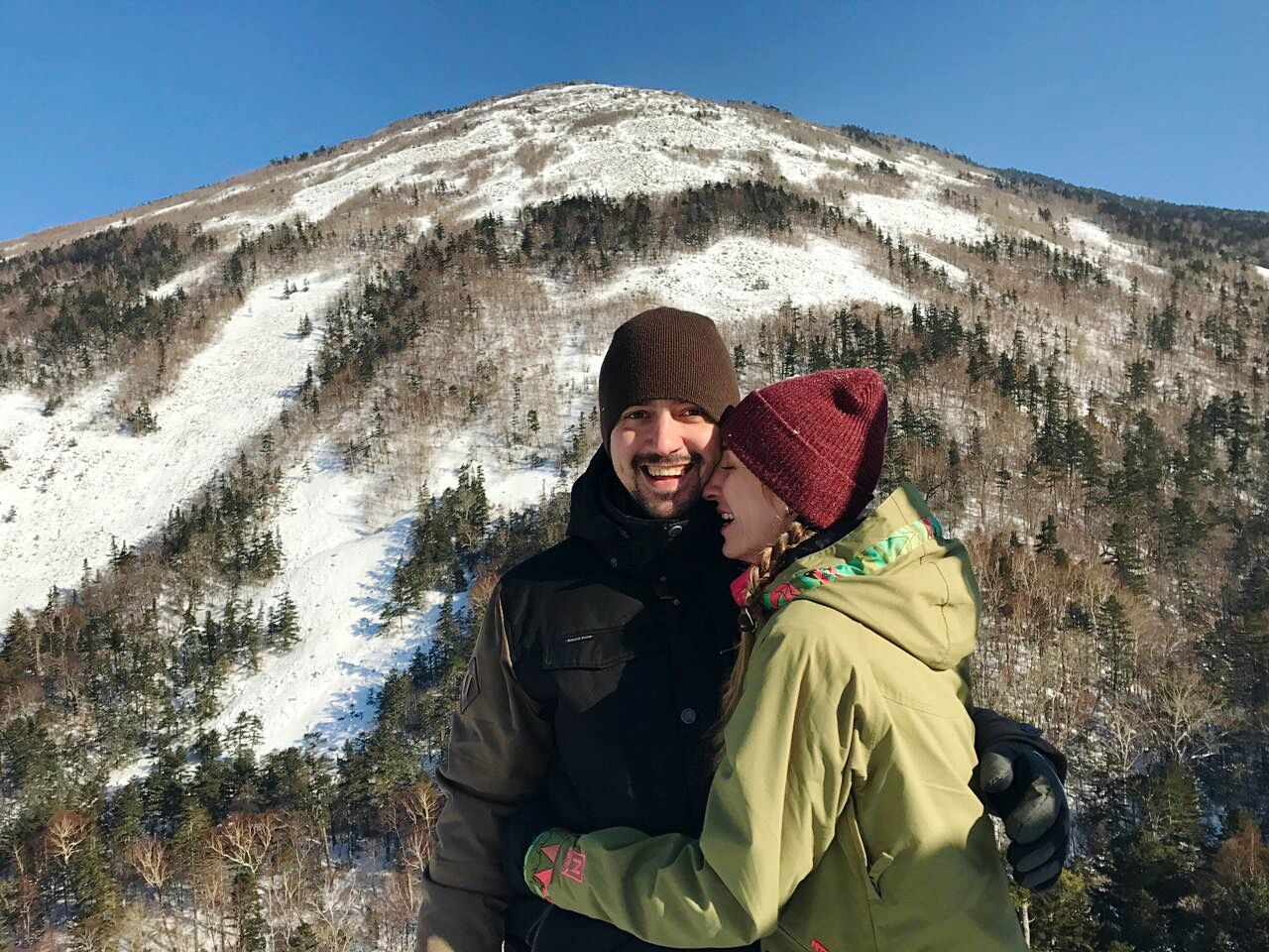 Portrait Of A Young Couple Against Snow Covered Mountain