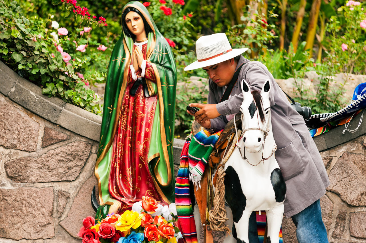 MEXICO CITY - MARCH 30: Man with cellphone next to religious statue in Mexico City on March 30, 2013 Catholic Catholicism City Cross Culture Df Faith Guadalupe Hat Historic Holy Man Market Mary Mexican Mexico Mexicocity  Religion Religious  Sacred Spirituality Statue Symbol Urban Virgin