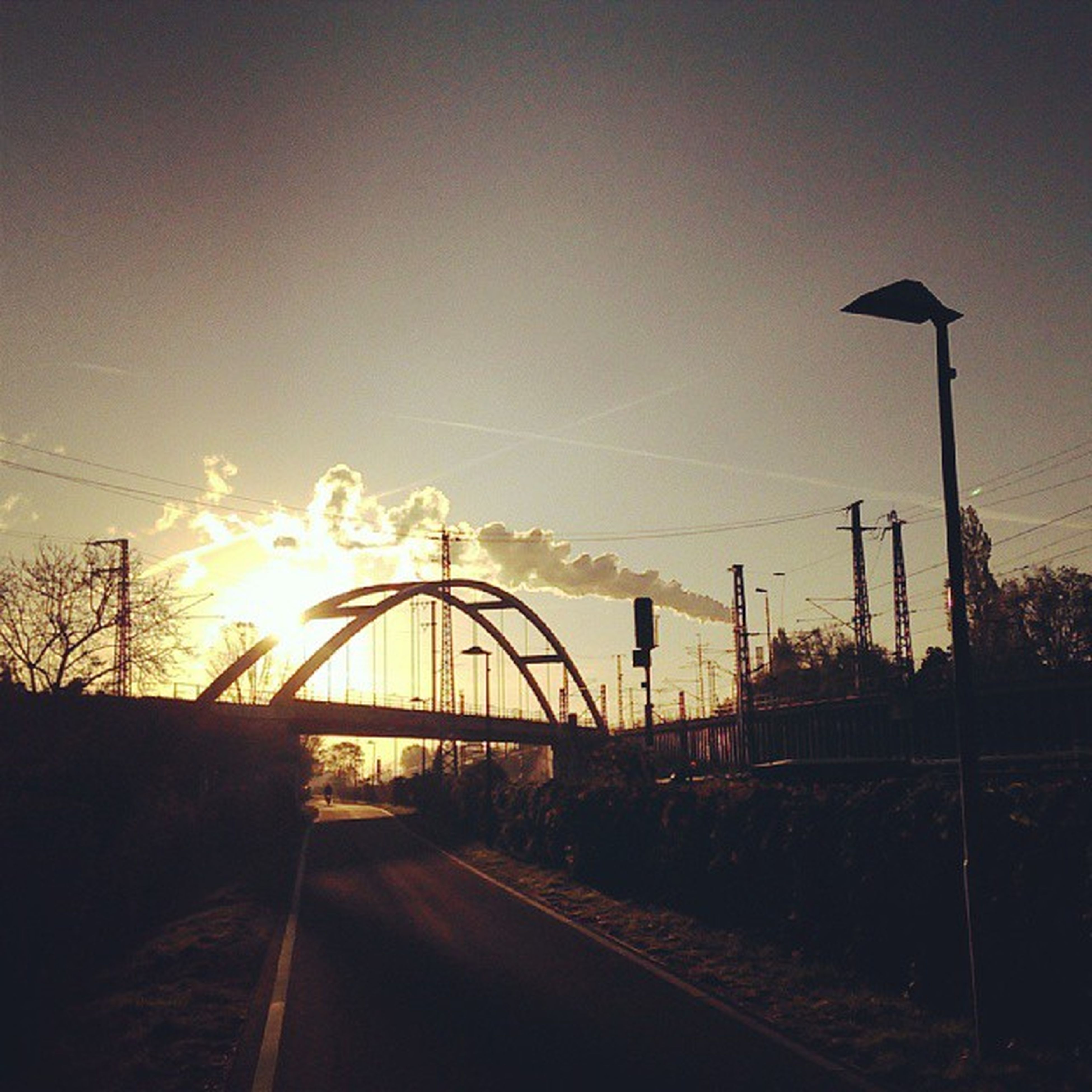 sunset, sun, sky, transportation, silhouette, road, the way forward, sunlight, connection, street light, electricity pylon, nature, sunbeam, outdoors, built structure, cloud - sky, orange color, tranquility, diminishing perspective, tree