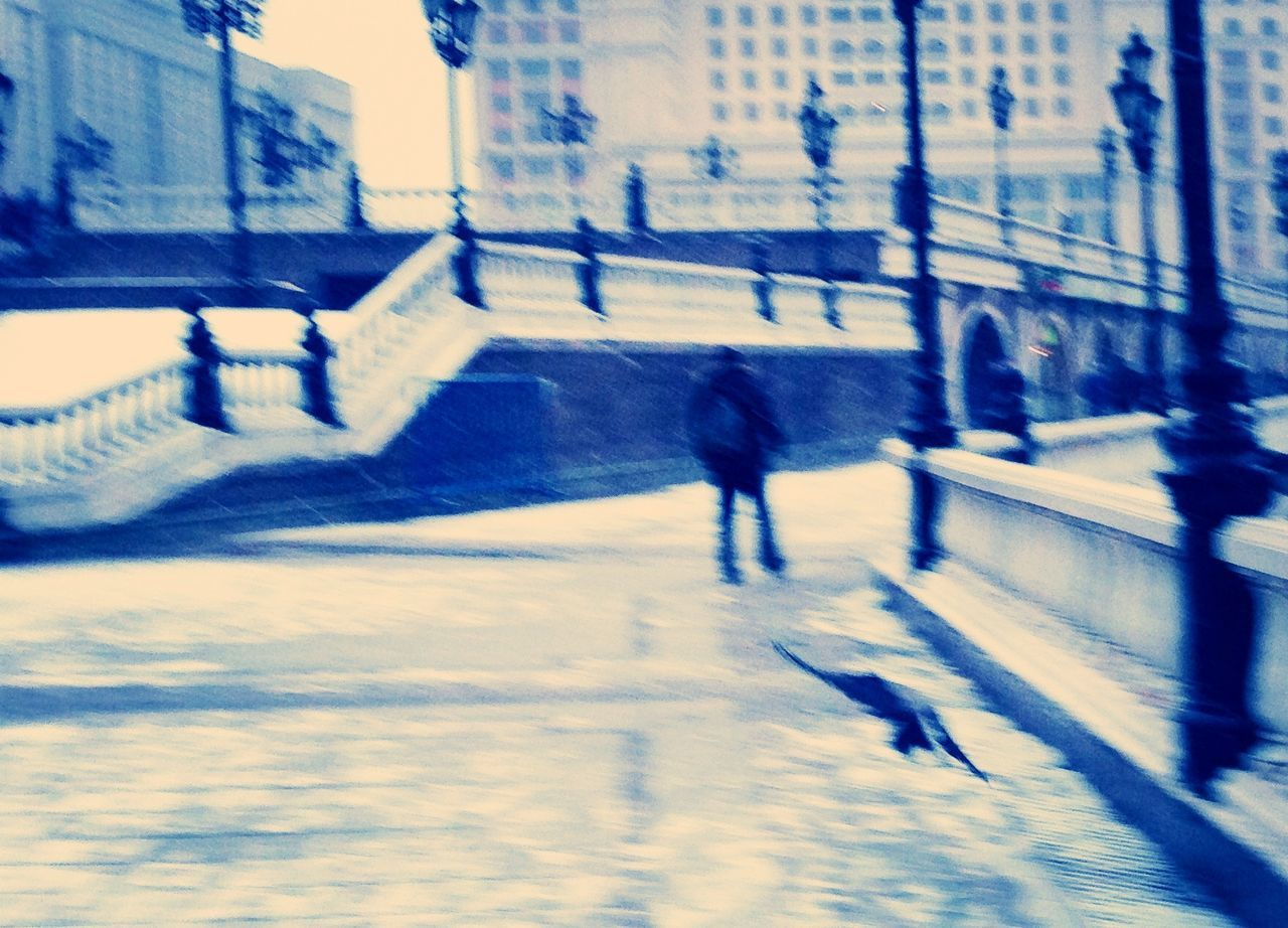 blurred motion, motion, winter, architecture, speed, city, real people, day, outdoors, street, building exterior, cold temperature, built structure, snow, one person, road, full length, nature, people