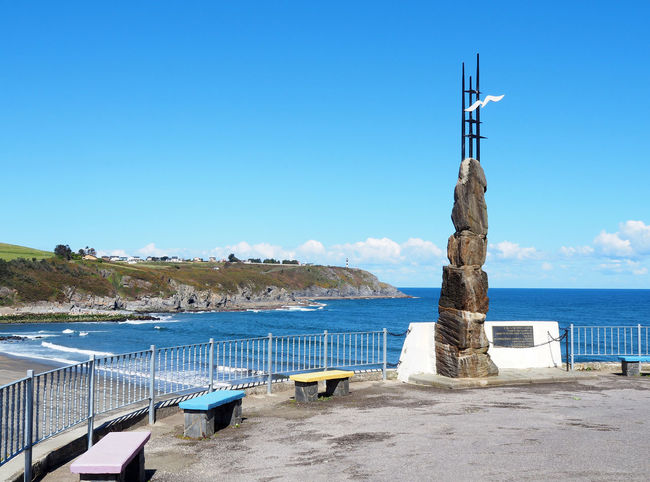 Lookout El Monolito with the monument to the emigrant in Navia, Asturias - Spain Asturias Beach Bench Blue Cantabrian Sea Coast Coastline Landmark Lookout Monument Nature Navia Ocean Outdoors Picturesque Sea Sea View Seaside Seats Sightseeing SPAIN Tourism Travel View Water