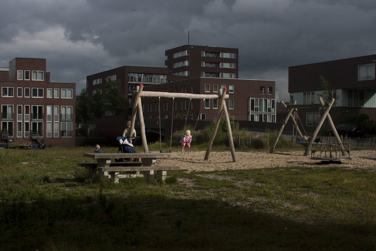 Woman and two children at a playground in Amsterdam Amsterdam Architecture building exterior built structure City cloud - sky day holland house ij ijburg lensculturestreets outdoors residential building sky storm cloud streetphoto streetphotography