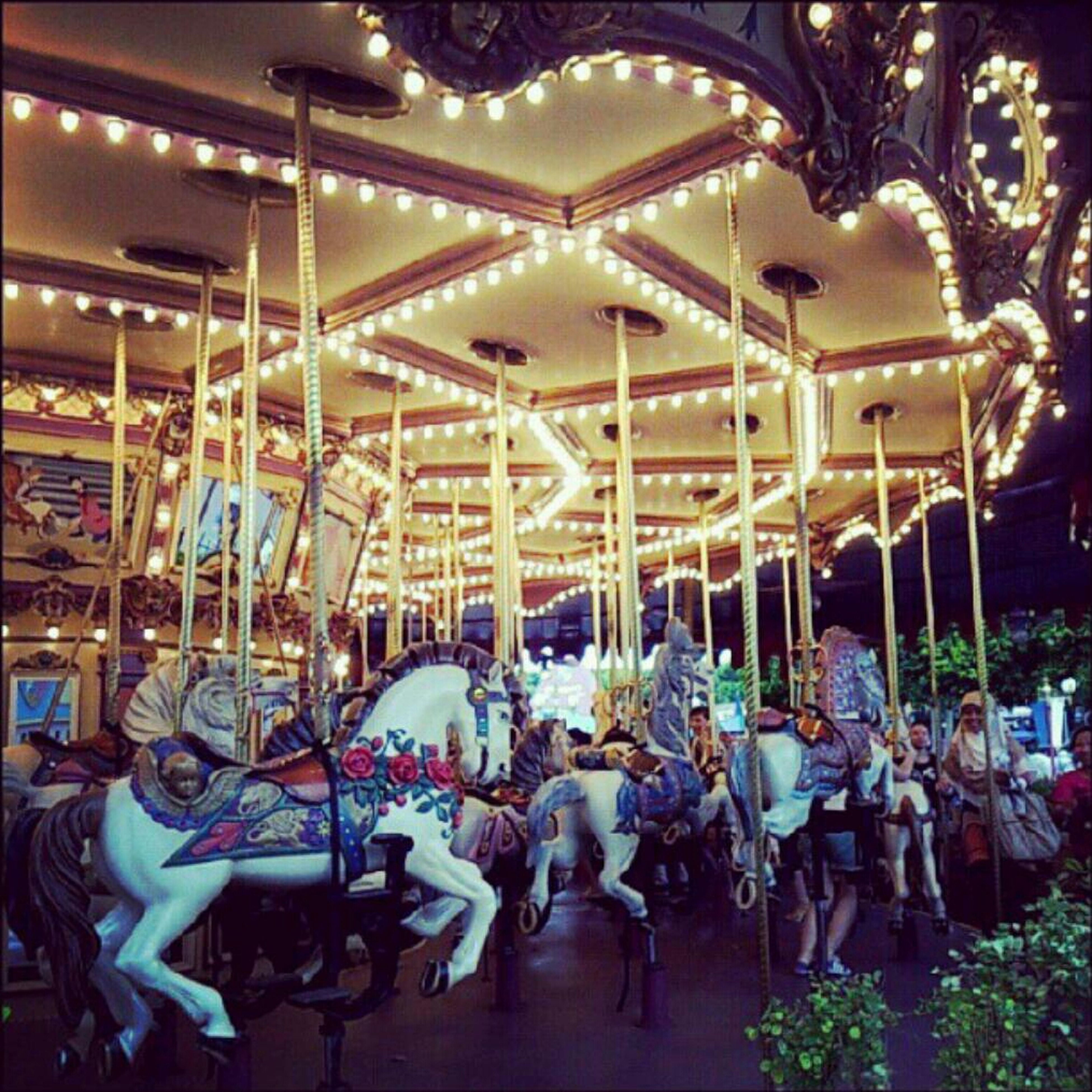 illuminated, night, chair, arts culture and entertainment, built structure, animal representation, men, amusement park, horse, carousel, lighting equipment, decoration, incidental people, tree, architecture, large group of people, leisure activity, outdoors, person