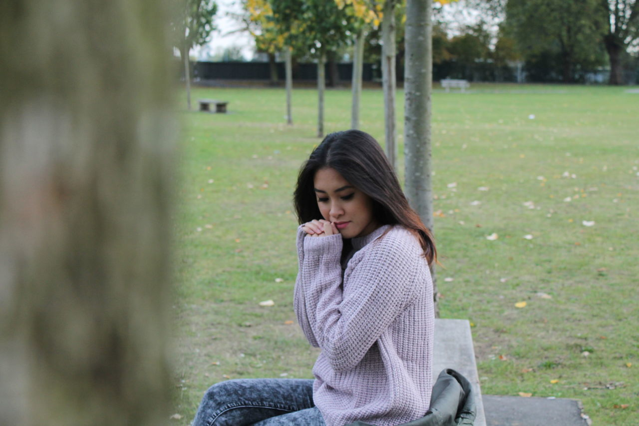 sitting, one person, day, long hair, outdoors, real people, park - man made space, lifestyles, young adult, women, young women, nature, people, adult